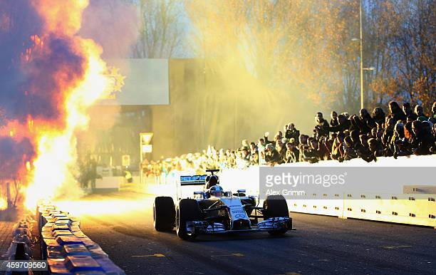 Firework explodes as Mercedes GP Formula One driver Lewis Hamilton of Germany drives his car during the annual Mercedes Benz Stars Cars event in...