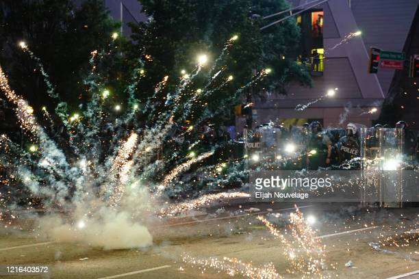A firework explodes in front of a police line during a protest in response to the police killing of George Floyd on May 30 2020 in Atlanta Georgia...