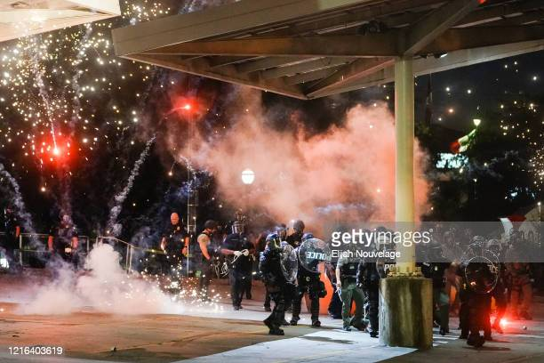 A firework explodes near a police line during a protest in response to the police killing of George Floyd on May 30 2020 in Atlanta Georgia Across...