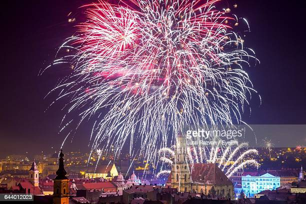 firework exploding over city against sky at night - lutai razvan stock pictures, royalty-free photos & images