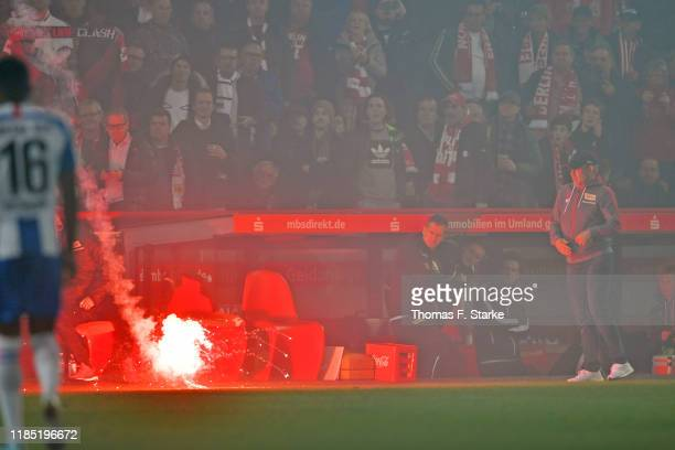 A firework lands infront of the substitutes bench of Union with head coach Urs Fischer during the Bundesliga match between 1 FC Union Berlin and...