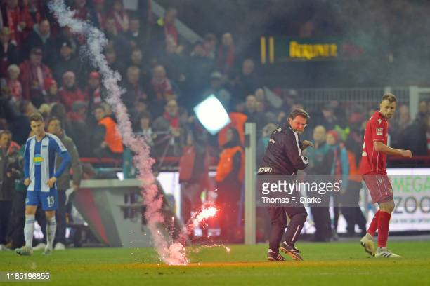A firework lands on the pitch while Marvin Friedrich of Union gets frightened after the Bundesliga match between 1 FC Union Berlin and Hertha BSC at...