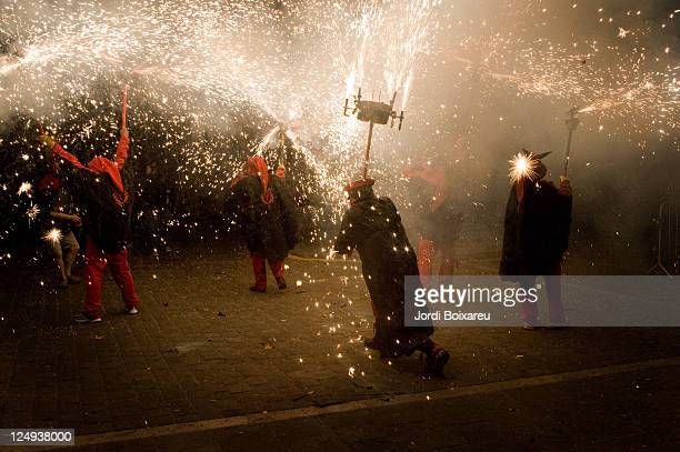 fireworks and devils on traditional 'correfoc' - devil costume stock photos and pictures