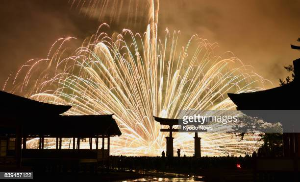 Fireworks are fired into the sky behind the gate and pavilions of Itsukushima Shrine a UNESCO World Cultural Heritage site on Aug 26 in the western...