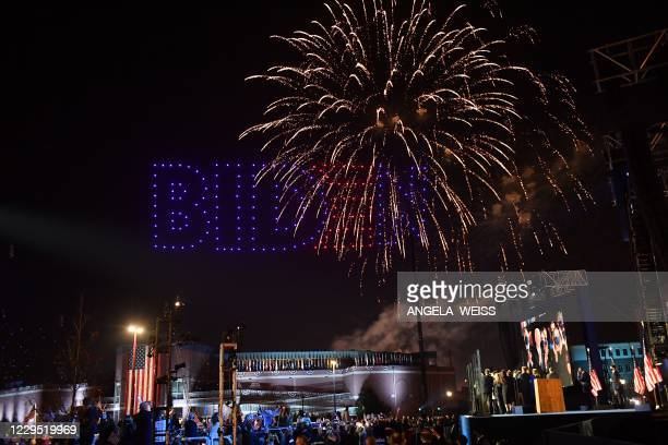 Fireworks are launched as illuminated drones spell BIDEN in the sky as US President-elect Joe Biden with his wife doctor Jill Biden alongside Vice...