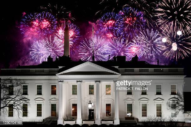 Fireworks are seen above the White House, with US Secret Service members watching from its roof, at the end of the Inauguration day for US President...