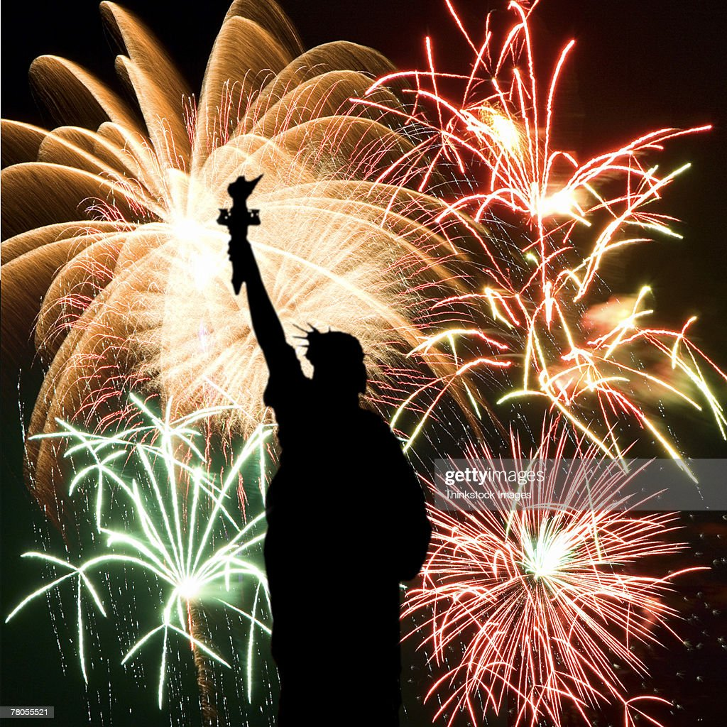 Fireworks behind Statue of Liberty silhouette : Stock Photo