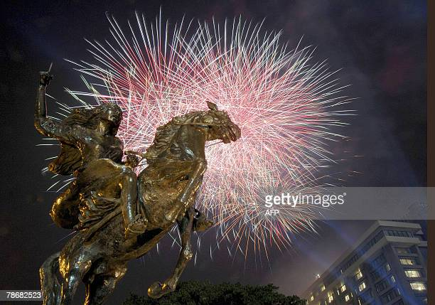 Fireworks brighten up the evening sky behind the monument of Filipino colonial hero Gabriela Silang and above the Makati business district of Manila,...