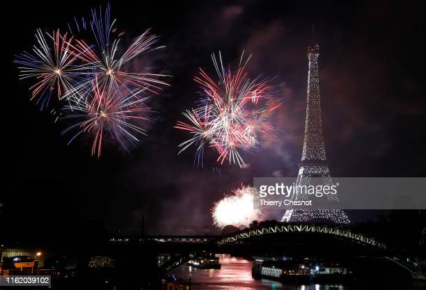 Fireworks burst around the Eiffel Tower as part of Bastille Day celebrations on July 14 2019 in Paris France This year the theme is the Fete de la...