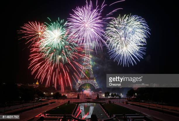 Fireworks burst around the Eiffel Tower as part of Bastille Day celebrations on July 14 2017 in Paris France The theme of the fireworks of this year...