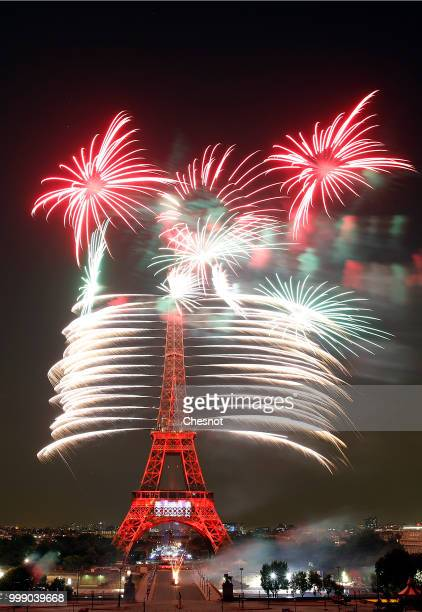Fireworks burst around the Eiffel Tower as part of Bastille Day celebrations on July 14 2018 in Paris France The theme of the fireworks of this year...