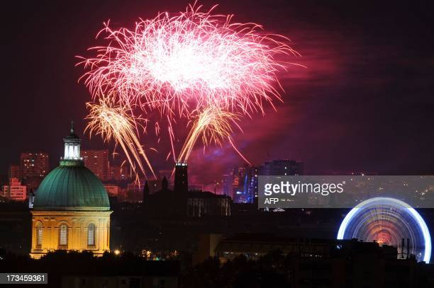 Fireworks burst between the dome of the La Grave Hospital and a ferris wheel on July 14 2013 in Toulouse as part of France's annual Bastille Day...