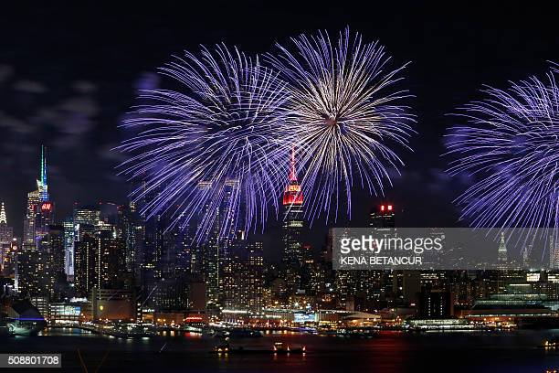 Fireworks burst over the New York skyline the Empire State Building lit up in red and gold in honor of the Chinese Lunar New Year as seen from...