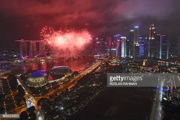 Fireworks burst over the skyline during an hourly display leading up to the final countdown for the New Year 2018 celebrations in Singapore on...