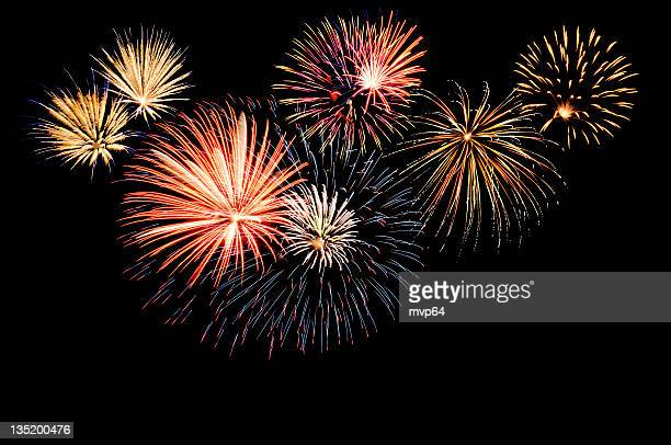 a fireworks display against the night sky - fireworks stock pictures, royalty-free photos & images