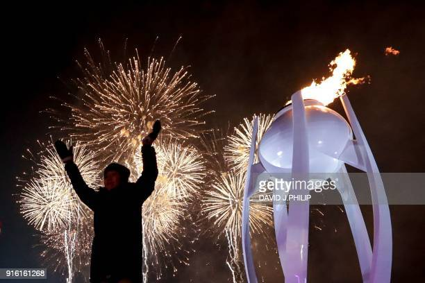 TOPSHOT Fireworks erupt as the cauldron is lit with the Olympic flame during the opening ceremony of the Pyeongchang 2018 Winter Olympic Games at the...