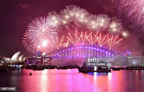 Fireworks erupt over Sydney's iconic Harbour Bridge and Opera House during the New Years Eve fireworks show in Sydney on January 1 2017 / AFP / PETER...