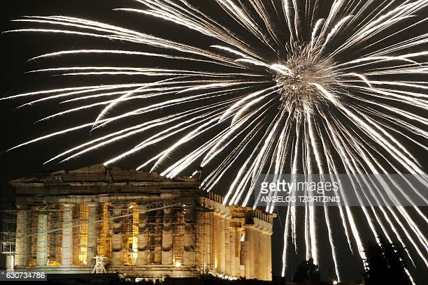 TOPSHOT Fireworks explode above the ancient Parthenon temple atop the Acropolis hill during New Year celebrations in Athens on January 1 2017 / AFP /...