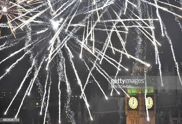 Fireworks explode above The Elizabeth Tower also known as 'Big Ben' during the New Year celebrations in central London just after midnight on January...