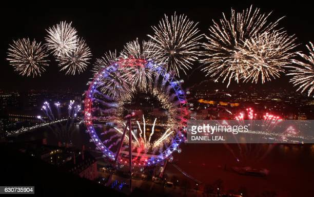 TOPSHOT Fireworks explode around The Elizabeth Tower also known as 'Big Ben' and the London Eye during New Year's celebrations in central London just...