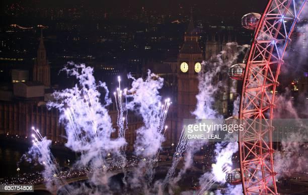 Fireworks explode around The Elizabeth Tower also known as 'Big Ben' and the London Eye during New Year's celebrations in central London just after...