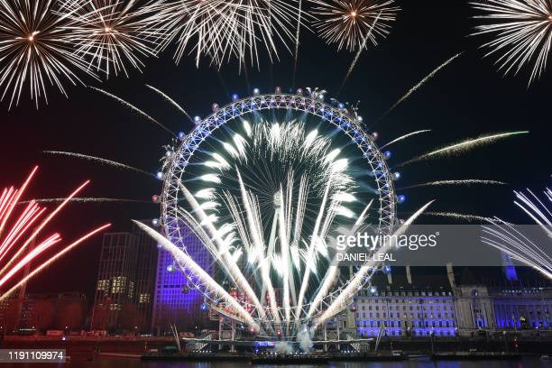 Fireworks explode around the London Eye during New Year's celebrations in central London just after midnight on January 1, 2020.