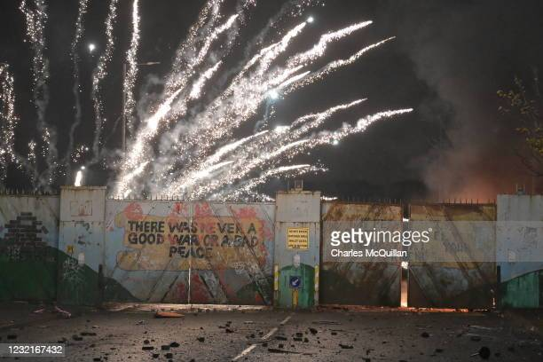 Fireworks explode as youths exchange projectiles through the Peace Gate during clashes at the Springfield Road/Lanark Way interface on April 7, 2021...