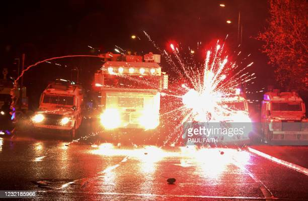 Fireworks explode at police vehicles after being fired at police officers with a water cannon during clashes with nationalist youths in the...