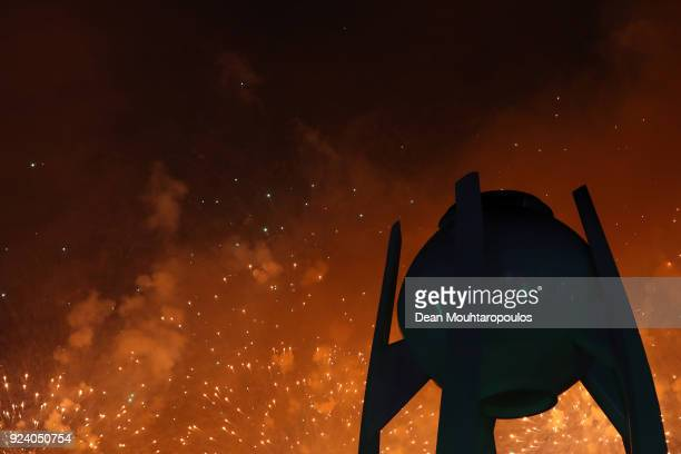 Fireworks explode behind the extinguished Olympic flame near the conclusion of the Closing Ceremony of the PyeongChang 2018 Winter Olympic Games at...