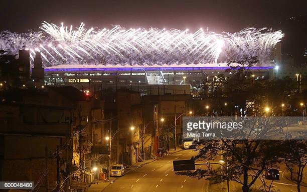Fireworks explode behind the MetroMangueira favela community during the Opening Ceremony of the Rio 2016 Paralympic Games at Maracana Stadium on...
