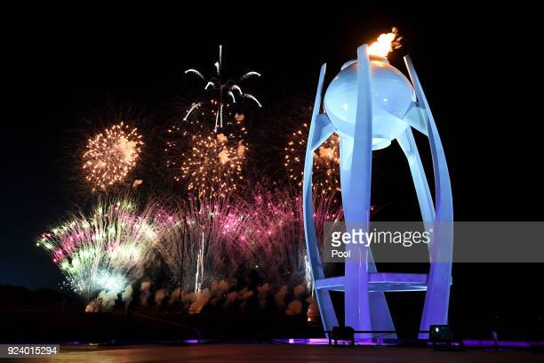 Fireworks explode behind the Olympic flame at the start of the Closing Ceremony of the PyeongChang 2018 Winter Olympic Games at PyeongChang Olympic...