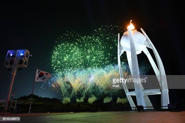 Fireworks explode behind the Olympic flame during the Closing Ceremony of the PyeongChang 2018 Winter Olympic Games at PyeongChang Olympic Stadium on...