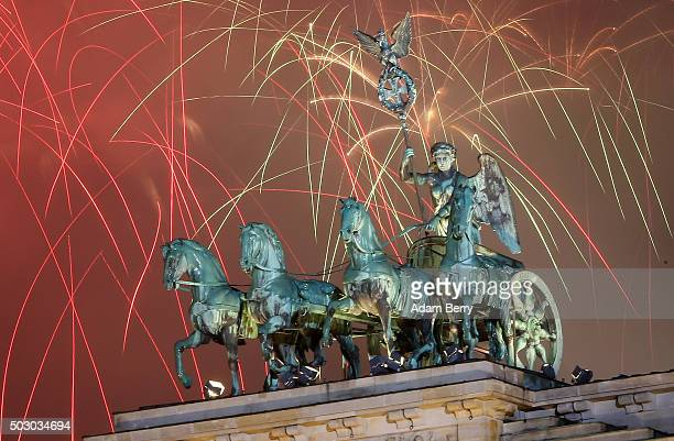 Fireworks explode behind the Quadriga statue atop the Brandenburg Gate on January 1 2016 in Berlin Germany After the terrorist attacks in Paris the...