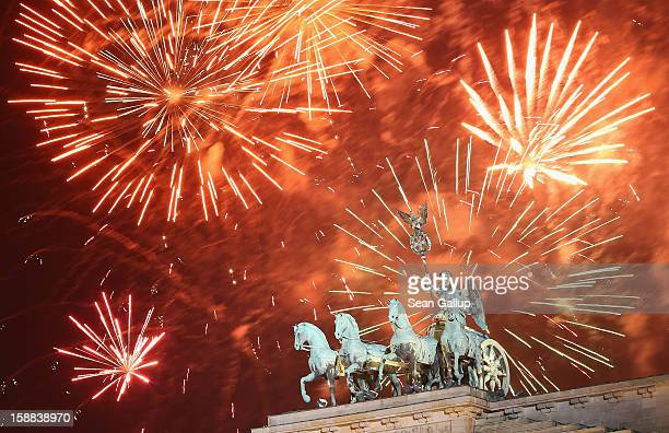 Fireworks explode behind the Quadriga statue on top of the Brandenburg Gate shortly after midnight on January 1 2013 in Berlin Germany Tens of...
