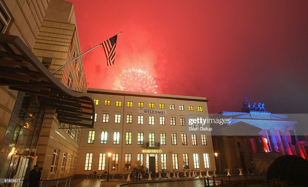 Fireworks explode behind the U.S. flag hanging from the front facade of the new U.S. embassy near the Brandenburg Gate (R) at the official opening ceremony and celebration of the embassy on July 4, 2008 in Berlin, Germany. Architectural critics claim the embassy, designed by American architect Moore Ruble Yudell, offers little in architectural innovation or design.
