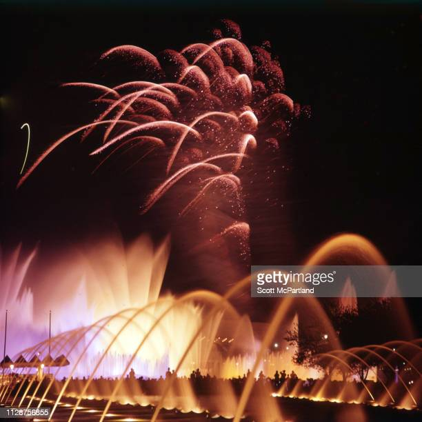 Fireworks explode in the night sky over illuminated fountains in Flushing Meadows Park during the World's Fair in Queens New York New York June 1965