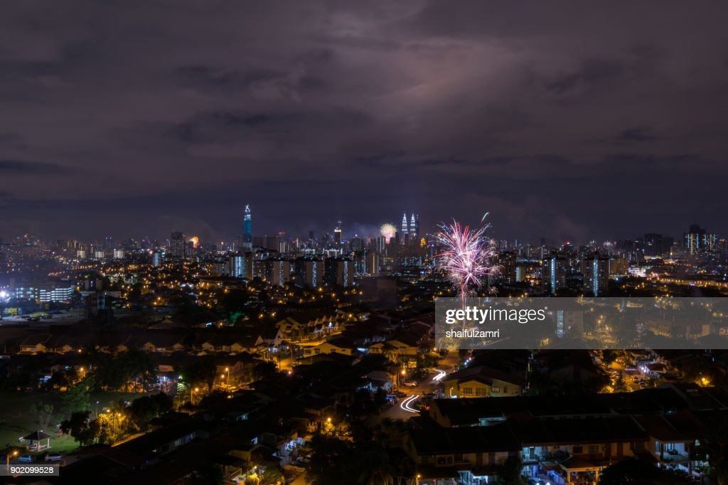Fireworks explode near Malaysia's landmark Petronas Twin Towers and residential area during New Year celebrations in Kuala Lumpur. : Stock Photo