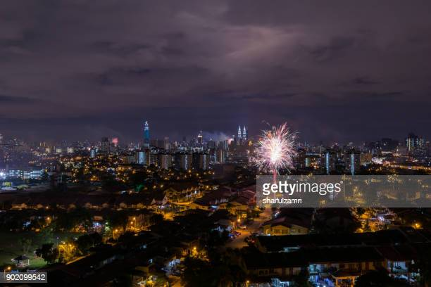 Fireworks explode near Malaysia's landmark Petronas Twin Towers and residential area during New Year celebrations in Kuala Lumpur.