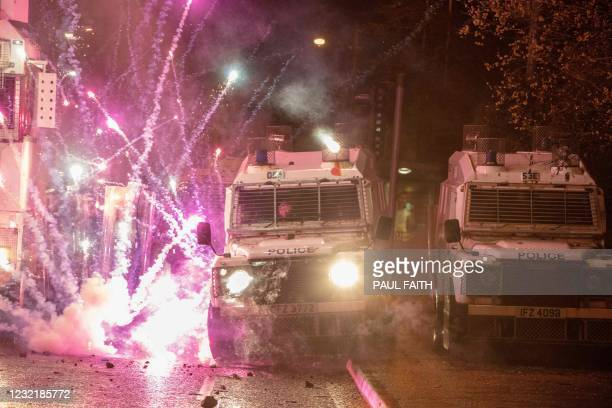 Fireworks explode on police vehicles after being fired at police officers during clashes with nationalist youths in the Springfield Road area of...