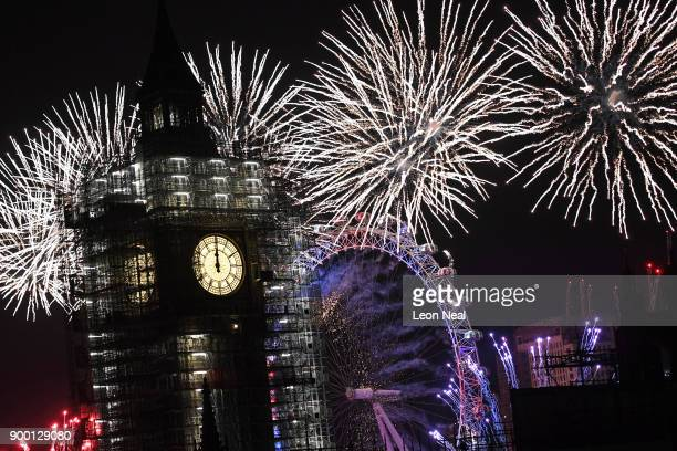 Fireworks explode over Big Ben and the giant Ferris wheel of the London Eye at midnight as thousands gather to ring in the near year on January 1...