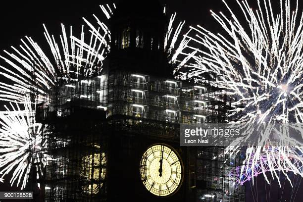 Fireworks explode over Big Ben at midnight as thousands gather to ring in the near year on January 1 2018 in London England Crowds lined the banks of...