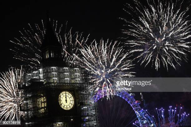 Fireworks explode over Big Ben clock and the giant Ferris wheel of the London Eye at midnight as thousands gather to ring in the near year on January...