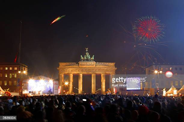 Fireworks explode over the Brandenburg Gate at the stroke of midnight December 31 2003 in Berlin Germany Revellers gathered in the streets to ring in...