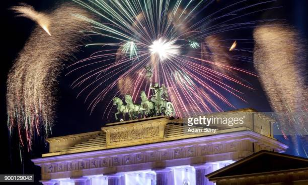 Fireworks explode over the Brandenburg Gate during New Year's festivities on January 1 2018 in Berlin Germany Tens of thousands of revelers gathered...