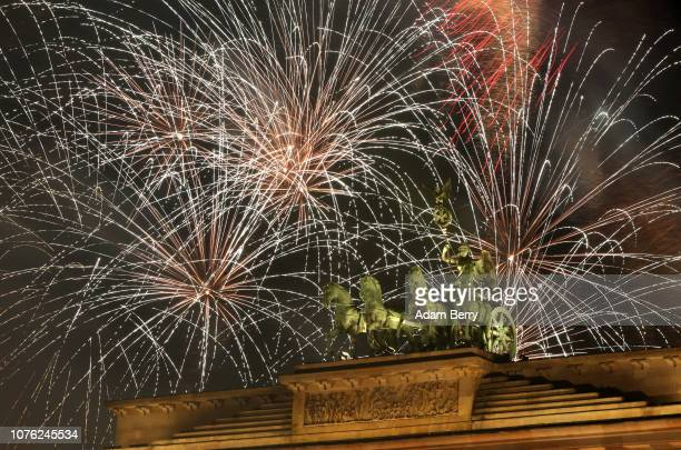 Fireworks explode over the Brandenburg Gate on January 1 2019 in Berlin Germany Every year hundreds of thousands of spectators gather for New Year's...