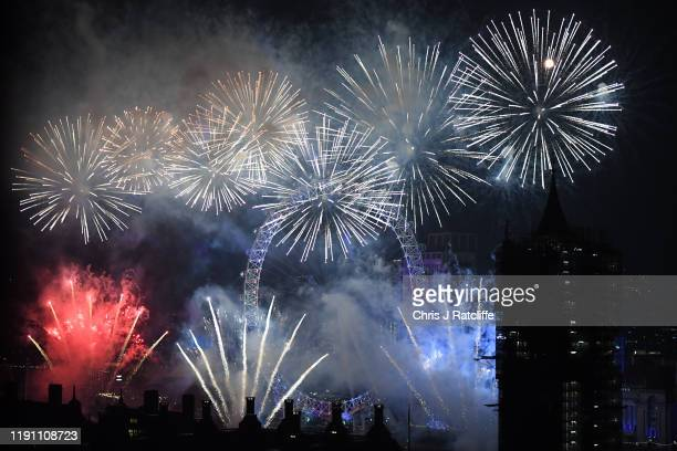 Fireworks explode over The Coca-Cola London Eye, Westminster Abbey and Elizabeth Tower near Parliament as thousands of revelers gather along the...