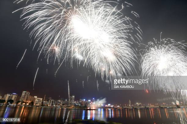 TOPSHOT Fireworks explode over the Ebrie lagoon during New Year celebrations in Abidjan on January 1 2018 / AFP PHOTO / Sia KAMBOU