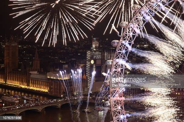 Fireworks explode over The London Eye and Elizabeth Tower near Parliament as thousands of revelers gather along the banks of the River Thames to ring...