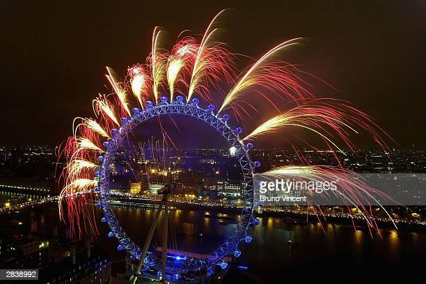 Fireworks explode over the London Eye and Westminster landmark Big Ben at the stroke of midnight December 31 2003 in central London Revellers...