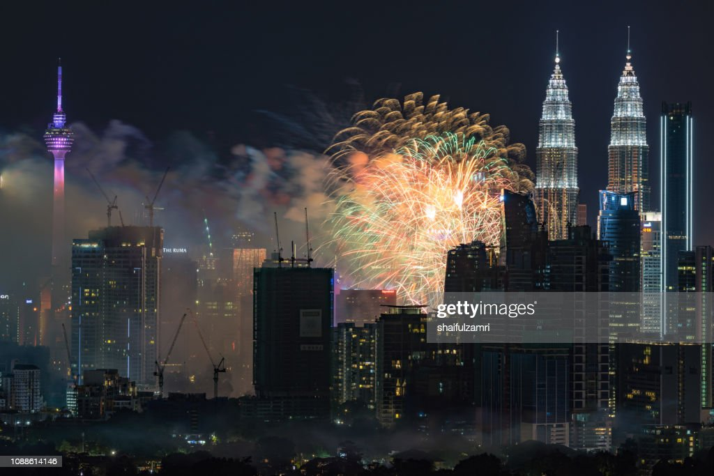 Fireworks explode over the Petronas Twin Towers during the midnight display on New Year's Eve in Kuala Lumpur, Malaysia. : Stock Photo